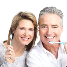 An older married couple holding toothbrushes.