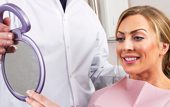 Woman and dentist examine smile in mirror