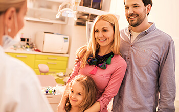 Smiling family of three in dental office