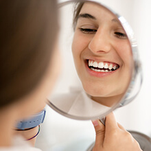 Girl examining perfect smile in mirror