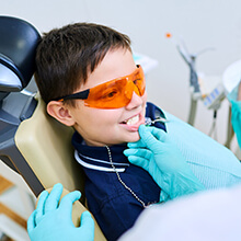 Young boy in safety glasses receives dental sealants