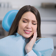 Woman in dental chair holding cheek in pain