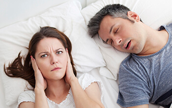 Snoring man and woman covering ears in bed