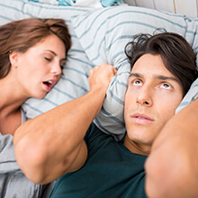 Snoring woman and man covering ears in bed