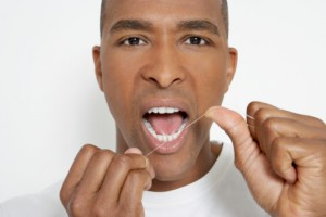 Man flossing teeth, portrait