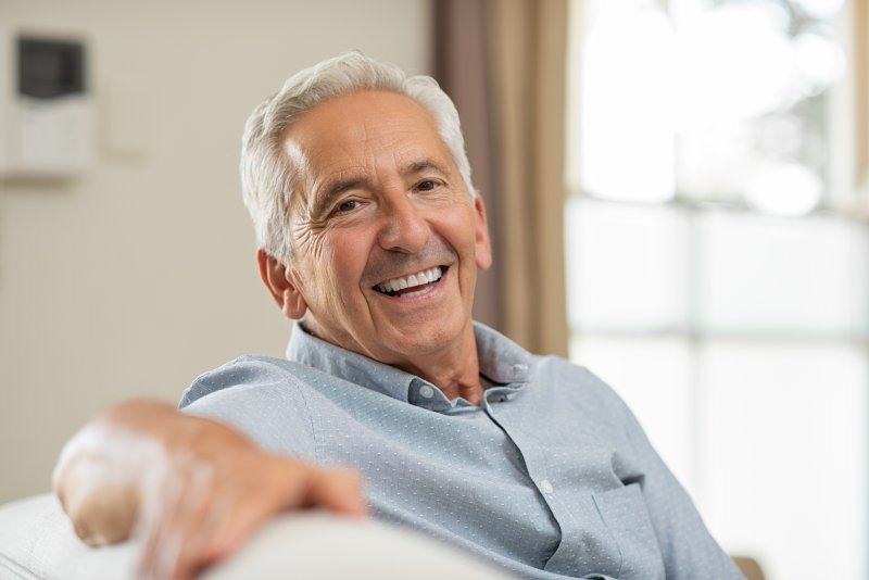 an older man sitting on a couch and smiling