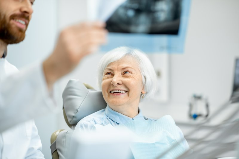 an older woman smiles while listening to her dentist during a checkup after receiving dental implants