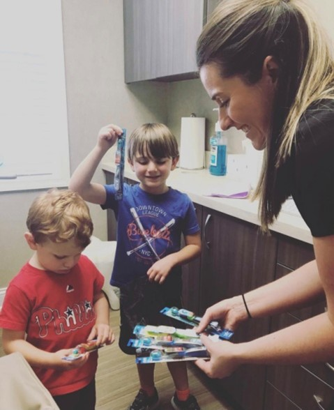 Dental hygienist helping kids pick out toothbrush